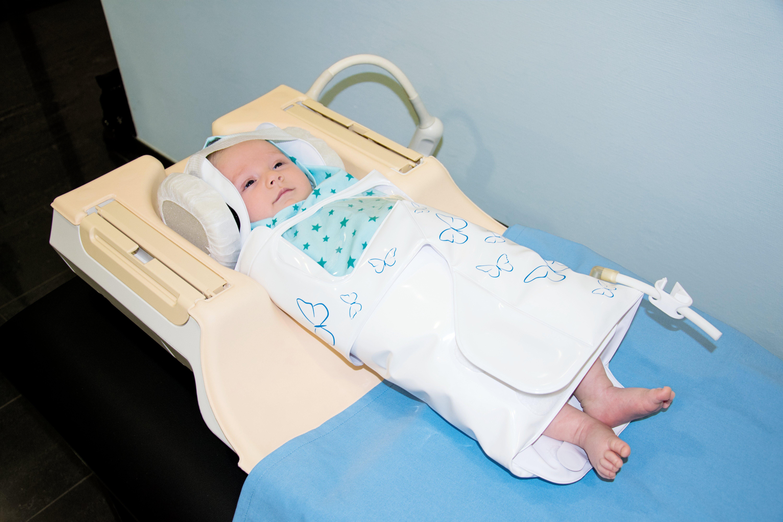 Abb. 1: Neugeborenes mit Lagerungshilfe in Kopfspule